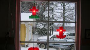 Anneli Lehtosen ikkunassa roikkuvat punaiset jouluvalot joissa risti, sydän ja ankkuri