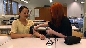 Valmistuvat sairaanhoitajat mittaavat verenpainetta.