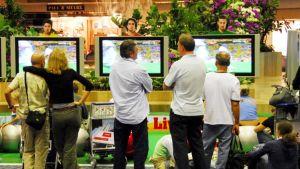 Ihmiset katsovat lentokentällä jalkapallon MM-kisoja televisiosta