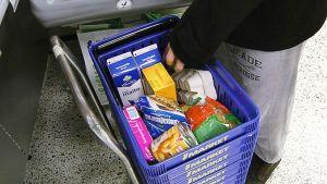 Asiakas nostamassa tavaroita ostoskorista kassahihnalle.