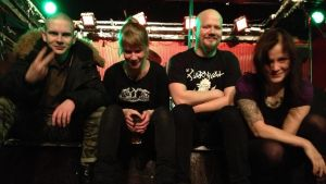 punk-yhtye istuu lavan reunalla.