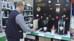 Myyjä asettelee kahvikonetta