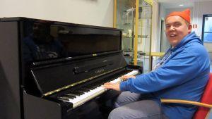 Kuvassa tonttupäinen mies soittamassa pianoa