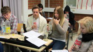 Kuvassa lukiolaisia puhaltelemassa limsapulloihin