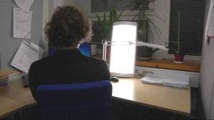 Mies istuu kirkasvalolampun loisteessa.