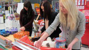 Kuvassa tytöt paketoivat lahjoja marketissa