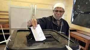Mies tiputtamassa äänestyslappua sille tarkoitettuun laatikkoon.