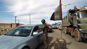 Sotilaat tarkastavat ajoneuvoja tiellä.