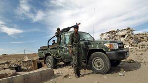 Sotilaita ja lava-auto johon on asennettu suuri konekivääri.