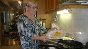 Kuvassa nainen esittelee lautasella olevaa sokeritinaa