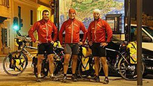 Kuvassa kolme miestä polkupyörien kanssa