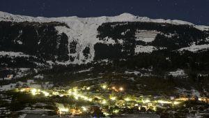 Pimeällä kuvattu kylä vuoren rinteellä