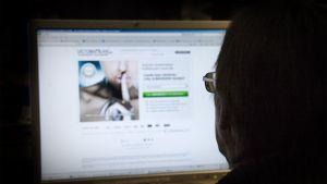 Mies istuu pimeässä monitorin ääressä