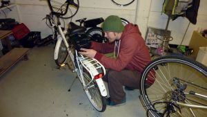 Jyri Arola asentaa polkupyörään sähkömoottoria.