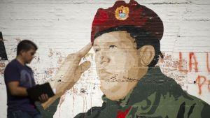 Mies kävelee Hugo Chavezia esittävän seinämaalauksen ohi Caracasissa.