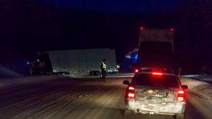 Raskas ajoneuvo ojassa, poliisi ohjaa liikennettä onnettomuuspaikalla.