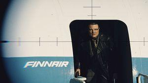 Lentokonekaappaaja poistuu Finnairin koneesta. Hänet on kuvattu aseen tähtäimen läpi.