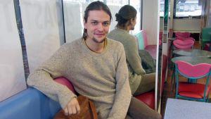 Mikael Saari hymyilee kahvilassa.