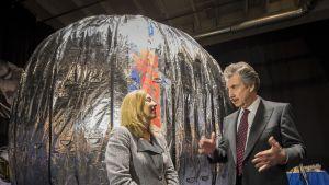 NASAn Lori Garver ja Bigelow Aerospace -yhtiön perustaja Robert T. Bigelow keskustelevat hopeisen BEAM-moduulin edessä.
