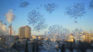 Lumikiteitä ikkunassa, taustalla Tampereen keskusta