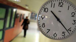Kello käytävän seinällä, taustalla kävelee ihminen.