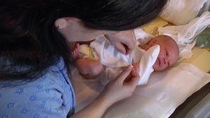 Äiti pukee vastasyntynyttä vauvaa Naistenklinikalla.