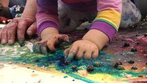 Lapsi koskettaa paperin päällä olevaa mustikkaa.