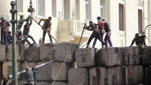 Mellakoivat ihmiset koittavat kangeta muuriin aukkoa