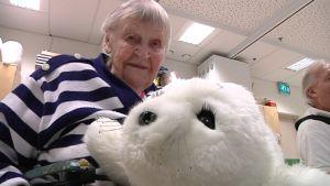 kuvassa mummo sylissään paro-hyljerobotti