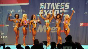 Fitness-kilpailijoita lavalla palkintoineen, Annu Hyökyvaara oikealla