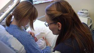 Katarina Guldbrand auttaa Riitta Huppea imettämään vauvaansa.
