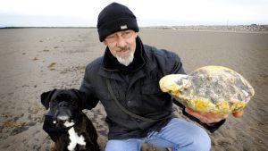 Ken Wilman kimpale ambraa kädessään - vierellä Madge-koira.