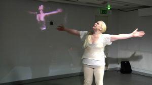 Valkoisiin pukeutunut näyttelijä lavalla seisomassa kädet levällään.