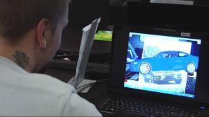 Opiskelija katsoo tietokonenäytöltä virtuaalikuvaa autosta