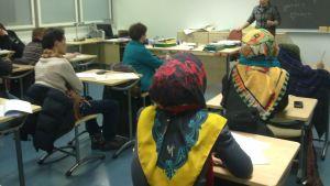 Kuvassa pakolaisia ja vapaaehtoistyöntekijöitä farsin kielen oppitunnilla.