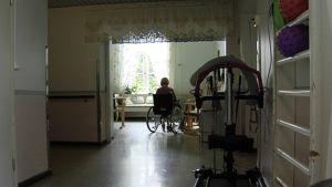 Yksinäinen vanhus istuu pyörätuolissa.