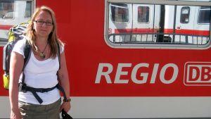 Kuvasa nainen seisoo juna-asemalla takanaan juna.