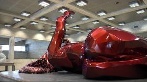 Kirkkanpunainen ja kiiltävä pintainen veistos makaavasta naisesta.
