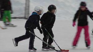 Kaksi poikaa pelaa jääkiekkoa kypärät päässä.