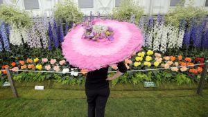 Valtavaan kukkahattuun pukeutunut nainen katsoo kukkanäyttelyä Chelseassa.