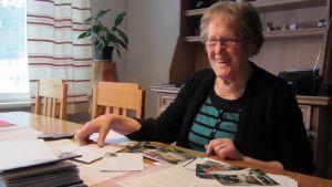 Kuvassa Kerttu Koskimaa istumassa pöydän ääressä edessään kirjeitä ja valokuvia
