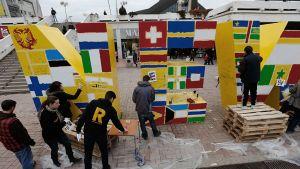 Ihmisiä aukiolla maalamassa lippuja suuriin keltaisiin kirjaimiin.