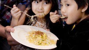 Lapset syövät ravintolassa Hongkongissa.