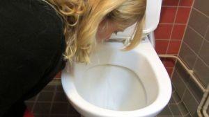 Nainen kumartuneena vessanpöntön ääreen oksennusasennossa.
