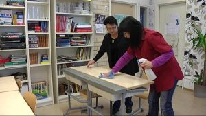 Kiinasta Suomeen muuttanut Shu-Ling Wang siivoaa koulun pulpettia.