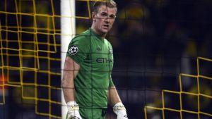Manchester Cityn Joe Hart katselee maaliverkon läpi.
