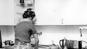 Nainen tiskaamassa keittiössä 1960-luvulla.