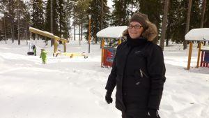 Riitta Kettunen seisoo leikkipuiston keskellä. Taustalla leikkii kaksi lasta.