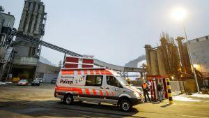 Poliisit päivystävät puunjalostustehtaan pihassa Sveitsin Menznaussa keskiviikkoiltana.