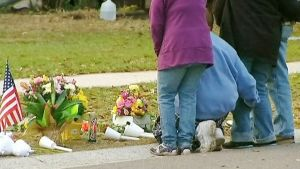 Maannielemän vieneen miehen perheenjäsenet ja ystävät laskevat kukkia talon edustalla sijaitsevalle muistopaikalle 3. maaliskuuta 2013.